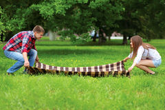 Young couple straightens the plaid for picnic together Stock Images