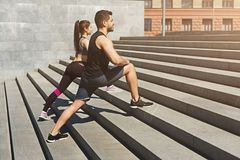 Young couple stretching legs in urban environment. Young couple stretching legs on stairs in urban environment, copy space Stock Photos