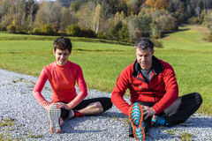 Young couple stretching out in mother nature. A couple training outdoors stretching in the countryside of the Bavarian Forest National Park, Germany Royalty Free Stock Images