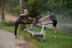 Young Couple Stretching Before Running In Wooded Forest Royalty Free Stock Photos