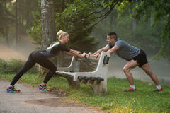 Young Couple Stretching Before Running In Wooded Forest Stock Photos
