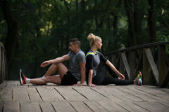 Young Couple Stretching Before Running In Wooded Forest Royalty Free Stock Photography