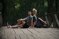 Young Couple Stretching Before Running In Wooded Forest Royalty Free Stock Photo