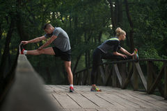 Young Couple Stretching Before Running In Wooded Forest Royalty Free Stock Image