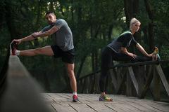 Young Couple Stretching Before Running In Wooded Forest Stock Image