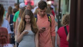 Young couple stroll along the busy city street and look at their mobiles in slo-mo