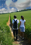 Young couple strolling. Through farmland on a summers day Royalty Free Stock Photo