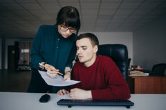 Young couple students guy and girl carefully looking at papers. Girl with glasses explaining something guy. Royalty Free Stock Image