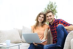 Young couple of students with laptop sitting on the couch Stock Photo