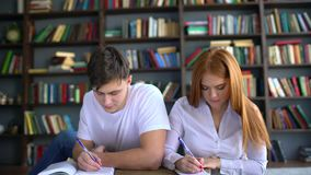 Young couple of students preparing to the exam. people, knowledge, education and school concept - students with books stock video