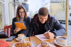 Young couple of students study in outdoor cafe, drink coffee tea, eat croissants, background is spring city street royalty free stock photos