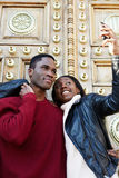 Young couple of students walking around the city in a day and making self portrait with mobile phone royalty free stock photo
