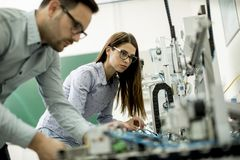Young couple of students working at robotics lab. Portrait of young couple of students working at robotics lab stock image