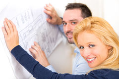 Young couple studying plans of their future house Royalty Free Stock Images