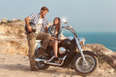Young couple. Stylish couple on a motorcycle. He put his foot on the exhaust pipe Stock Image
