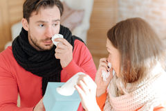 Young couple suffering from flu at home. Caring about each other. Ill empathetic young couple sitting in the bedroom and suffering from influenza while holding Stock Image