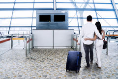 Young couple with suitcase at airport terminal Royalty Free Stock Images