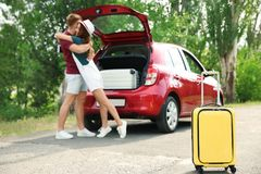 Young couple with suitcases near car Stock Images