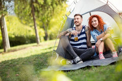 Young couple at summer camping. Young couple in front of tent at at music summer camp festival Stock Photo