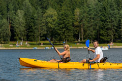 On pond young couple sitting in kayak Stock Photos