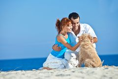 Young couple at sea side playing with their dog. Young couple, summertime, sea side, happy games with their dog Stock Photos