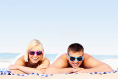 Young couple sunbathing at the beach Stock Photos