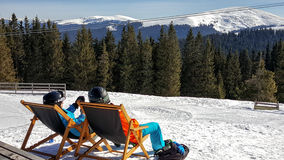 Young couple sunbathing at a ski resort Royalty Free Stock Photography