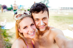Young couple sunbathing, taking selfie. Sunscreen on the nose. Stock Image