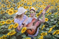 Young couple in sunflower field. Couple playing guitar and singing in sunflower field. Love, relationship and music concepts Stock Photography