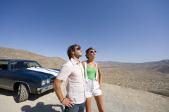 Young couple in sunglasses by car in desert, looking up Stock Photo