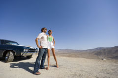 Young couple in sunglasses by car in desert, low angle view Stock Images