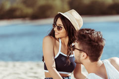 Young couple in sunglasses resting at sandy beach Royalty Free Stock Image