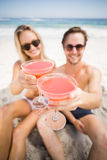 Young couple in sunglasses showing cocktail glass on the beach. Happy young couple sitting on the beach and showing cocktail glasses Royalty Free Stock Photography