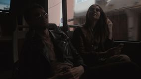 Tourists in a bus. A young couple in sunglasses sitting in a bus, moving along a city street stock footage