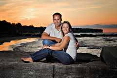 Young Couple Sunset. An attractive young couple posing on the beach at sunset Royalty Free Stock Image