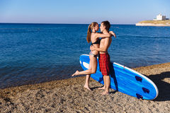 Young couple with sup board on the beach. Concept of sport, lifestyle Royalty Free Stock Photos