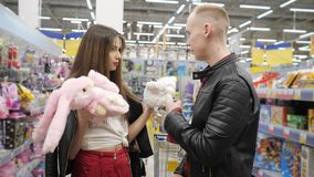 Young couple in supermarket is choosing teddy toy - pink teddy hare or polar teddy bear. Young couple guy and girl in supermarket is choosing teddy toy - pink stock video footage