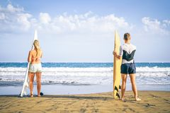 Young couple of surfers standing on the beach with surfboards preparing to surf on high waves - Healthy friends having fun royalty free stock photo