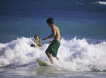 Young couple surfing in hawaii Stock Images