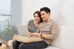 Young couple surfing on internet with laptop. Modern white apartment in background stock photo