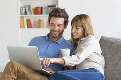 Young couple surfing on internet with laptop. Modern white apartment Royalty Free Stock Images