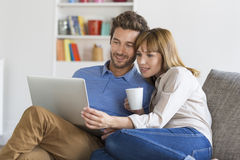 Young couple surfing on internet with laptop. Modern white apartment Royalty Free Stock Photos