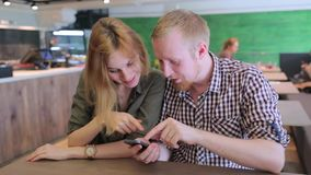 Young couple surfing the web looking at photos on mobile phone. In a cafe stock video footage