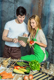 Young Couple Surfing the Web in the Kitchen Stock Image