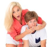 Young couple surprised. Young woman with surprised, shocked expression places her hands over a young man's mouth Stock Photography