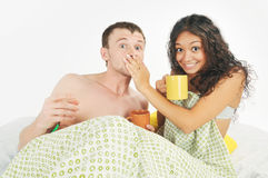Young couple surprised in bed Stock Image