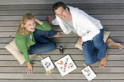 Young couple with sushi and drinks on decking, smiling, portrait, elevated view Stock Photo