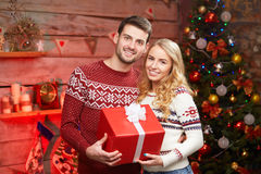 Young couple in sweaters embracing and holding red giftbox Royalty Free Stock Photo