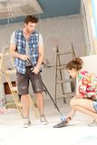 Young couple sweeping in house under construction. Men holding brush, women holding shovel Stock Photos