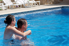 A young couple in the swimming  pool Stock Images
